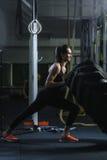 Istruttore muscolare potente di CrossFit della donna che fa allenamento della gomma alla palestra Immagine Stock