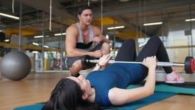 Istruttore nella palestra e giovani donne esili che fanno esercizio per le natiche - l'aumento di un corpo che si trova sopra la  video d archivio