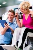 Istruttore in palestra che assiste esercitazione senior della donna immagine stock
