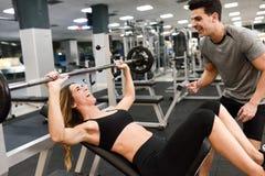 Istruttore personale che aiuta una giovane donna a sollevare i pesi immagini stock