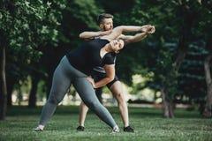 Istruttore personale che assiste esercitazione obesa della donna Fotografia Stock