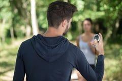 Istruttore personale che cronometra corridore femminile immagini stock libere da diritti