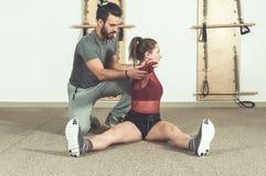 Istruttore personale maschio bello con una barba che aiuta la giovane ragazza di forma fisica ad allungare i suoi muscoli dopo l' Fotografie Stock