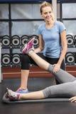 Istruttore sorridente che allunga la gamba della donna incinta Fotografia Stock
