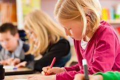 Istruzione - allievi alla scuola che fa compito Immagini Stock Libere da Diritti