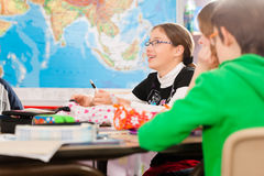 Istruzione - allievi alla scuola che fa il loro compito Immagine Stock