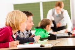 Istruzione - allievi ed insegnante che imparano alla scuola immagini stock libere da diritti