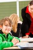 Istruzione - allievi ed insegnante che imparano alla scuola Immagini Stock