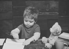 Istruzione alternativa Piccola scrittura del bambino in manuale Ragazzo diligente che impara le lettere r Fotografie Stock Libere da Diritti