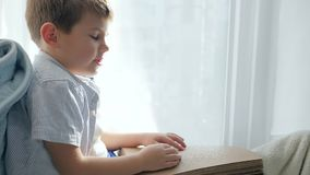 Istruzione del bambino cieco e facente male con il libro leggente cieco di Braille che si siede sul davanzale stock footage