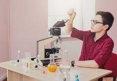 Istruzione del GAMBO L'adolescente fa la ricerca chimica Immagini Stock Libere da Diritti