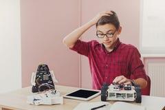 Istruzione del GAMBO Ragazzo che crea robot al laboratorio immagini stock