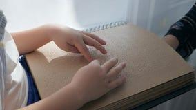 Istruzione del ` s dei bambini, uomo cieco che legge il libro di Braille stock footage