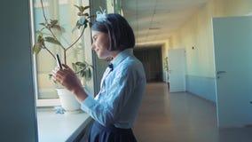 Istruzione della scolara con gli smartphones al concetto della scuola Anni dell'adolescenza della ragazza e smartphone usando che video d archivio
