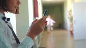 Istruzione della scolara con gli smartphones al concetto della scuola Anni dell'adolescenza della ragazza e smartphone usando che archivi video