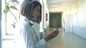 Istruzione della scolara con gli smartphones al concetto della scuola Ragazza e smartphone usando che fa una pausa la finestra in stock footage