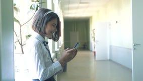 Istruzione della scolara con gli smartphones al concetto della scuola Ragazza e smartphone usando che fa una pausa la finestra in video d archivio