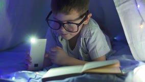 Istruzione a domicilio, ragazzo felice negli occhiali con la fiaba della lettura della torcia elettrica in tenda nello scuro