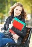 Istruzione e studio Allievo femminile felice Ragazza con i taccuini ed i libri di esercizi in parco all'aperto Fotografia Stock