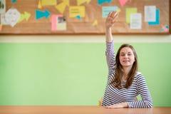 Istruzione, imparare e concetto degli adolescenti Studente che si siede nell'aula e che solleva mano immagini stock libere da diritti