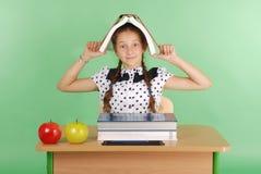 Istruzione, la gente, bambini e concetto della scuola - giovane ragazza della scuola che si siede ad uno scrittorio con un libro  Fotografia Stock