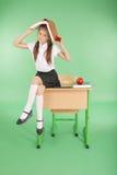 Istruzione, la gente, bambini e concetto della scuola - giovane ragazza della scuola che si siede sullo scrittorio con un libro s Fotografia Stock