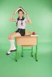 Istruzione, la gente, bambini e concetto della scuola - giovane ragazza della scuola che si siede sullo scrittorio con un libro s Fotografia Stock Libera da Diritti