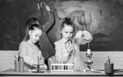 Istruzione scolastica Le ragazze della scuola studiano Bambini in aula con il microscopio e le provette Esplori le molecole biolo fotografia stock libera da diritti