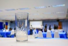 Isvatten i exponeringsglas i bakgrund för seminariumkonferensrum Välj fokusen med grunt djup av fältet Arkivbild