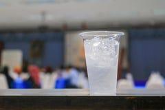 Isvatten i exponeringsglas-plast- i bakgrund för seminariumkonferensrum Välj fokusen med grunt djup av fältet Royaltyfria Bilder