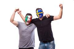 Itália contra a Suécia no fundo branco Os fan de futebol das equipas nacionais comemoram, dançam e gritam Fotos de Stock