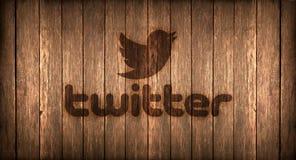 Itália, em novembro de 2016 - o logotipo de Twitter imprimiu no fogo em uma madeira Fotografia de Stock Royalty Free