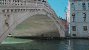 Itália, Veneza - em fevereiro de 2019: A gôndola com turistas está movendo-se sob a ponte de Rialto video estoque