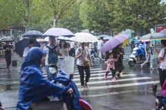 It's che piovono di mattina ed i pedoni che camminano tramite la strada passano tramite l'intersezione immagine stock libera da diritti