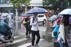 It's che piovono di mattina ed i pedoni che camminano tramite la strada passano tramite l'intersezione fotografia stock libera da diritti