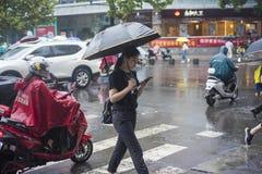 It's che piovono di mattina ed i pedoni che camminano tramite la strada passano tramite l'intersezione fotografie stock libere da diritti