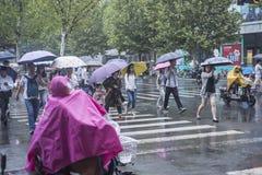 It's, das morgens regnen, und die Fußgänger, die durch die Straße gehen, überschreiten durch den Schnitt stockfoto