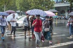 It's, das morgens regnen, und die Fußgänger, die durch die Straße gehen, überschreiten durch den Schnitt lizenzfreies stockfoto