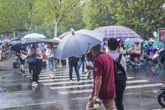 It's, das morgens regnen, und die Fußgänger, die durch die Straße gehen, überschreiten durch den Schnitt stockbild