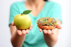It's duramente para escolher o conceito saudável do alimento, com a mão da mulher que guarda uma maçã verde e uma filhós da bom Imagens de Stock