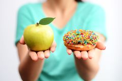It's hard to choose healthy food concept, with woman hand holding an green apple and a calorie bomb donut stock images