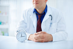 It's never too late for medical care. Young doctor with clock on the table - It's never too late for medical care Royalty Free Stock Photo