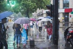 It's que llueve por la mañana, y los peatones que caminan a través del camino pasan por la intersección fotos de archivo