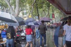 It's som regnar i morgonen och gångare som går till och med vägen, förbigår genomskärningen royaltyfri bild