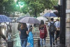 It's som regnar i morgonen och gångare som går till och med vägen, förbigår genomskärningen royaltyfria bilder