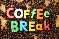 It's time for coffee break concept with colourful text on roasted coffee beans background stock photography