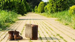 It's time to wander. Worn shoes and an old suitcase. Stock Photography