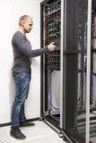 IT工程师大厦在datacenter的网络机架 免版税库存图片