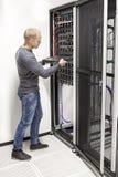IT顾问修造在datacenter的网络机架 免版税图库摄影
