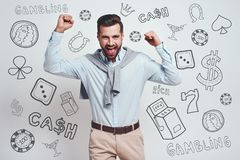 Free It Is All Mine! Happy Young Bearded Man Is Celebrating His Success With Raised Hands While Standing Against Grey Stock Images - 143372004